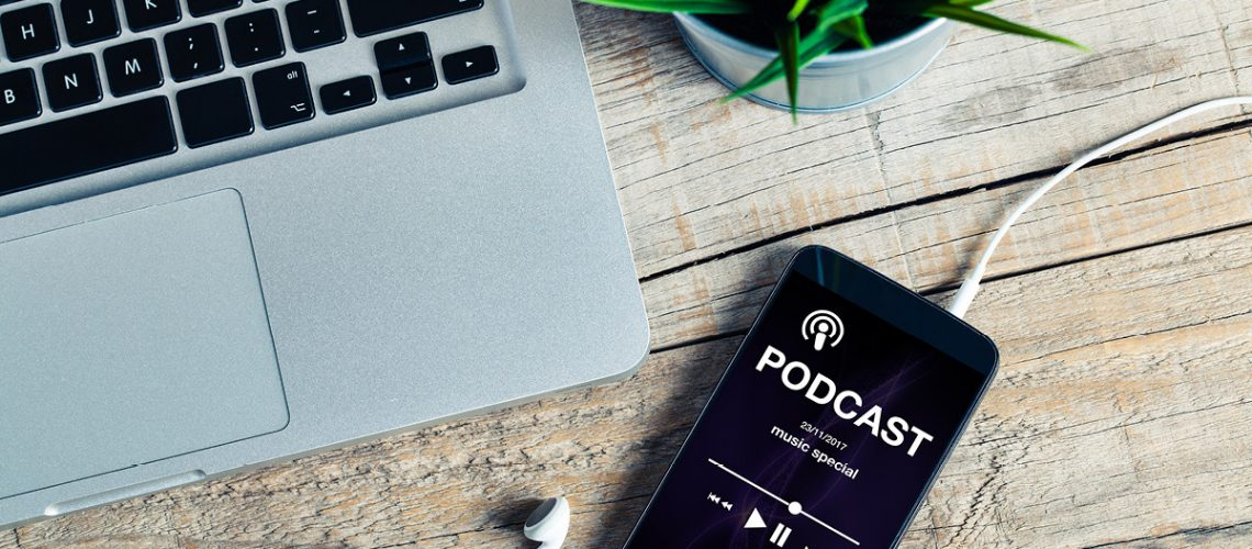 Mobile phone placed on a wooden desk with podcast app in the screen-iStock-879661826-1200x628